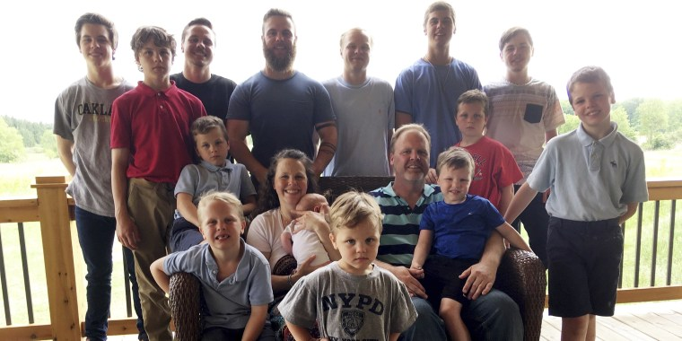 In this May 30, 2018 file photo, the Schwandt family poses for a photo at their farm in Lakeview, Mich. Standing from left are Tommy, Calvin, Drew, Tyler, Zach, Brandon, Gabe, Vinny and Wesley. Seated, starting at upper left are Charlie, Luke, mother Kateri holding Finley, father Jay with Tucker and Francisco in the foreground.