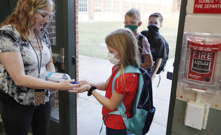 Wearing masks to prevent the spread of Covid-19, elementary school students use hand sanitizer before entering school for classes in Godley, Texas, on Aug. 5, 2020.
