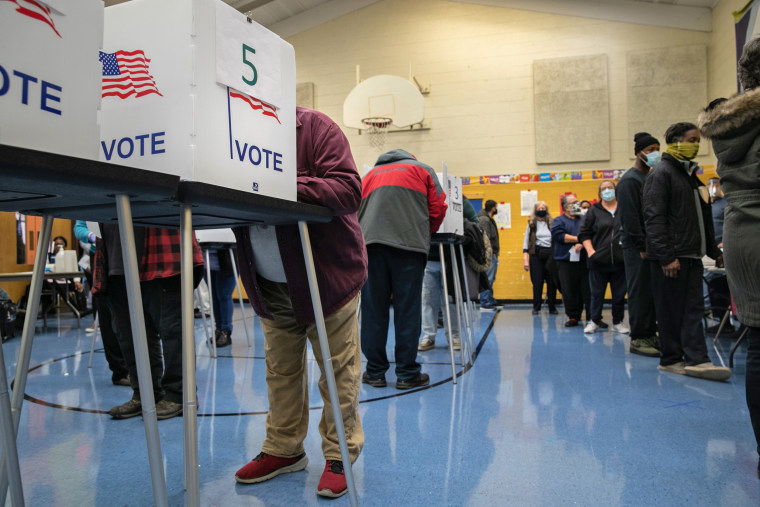 Voters fill out their ballots at a school gymnasium on Election Day in Lansing, Mich.