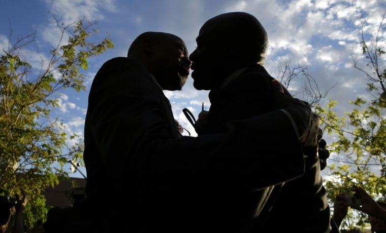 Image: Sherwood Howard, left, embraces Nevada State Sen. Kelvin Atkinson as they get married outside of the Marriage License Bureau in Las Vega