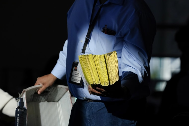 Image: An election worker distributes ballots as vote counting in the general election continues at State Farm Arena on Thursday, Nov. 5, 2020, in Atlanta.