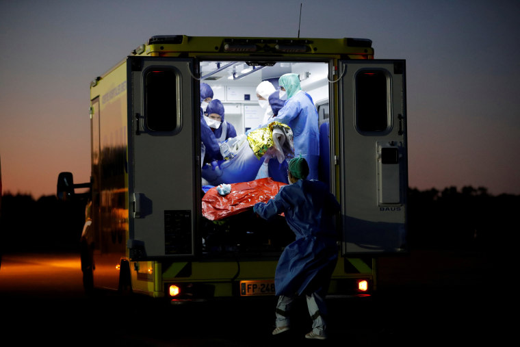Image: Medical staff members move a patient from a plane during a transfer operation of people suffering from the coronavirus disease