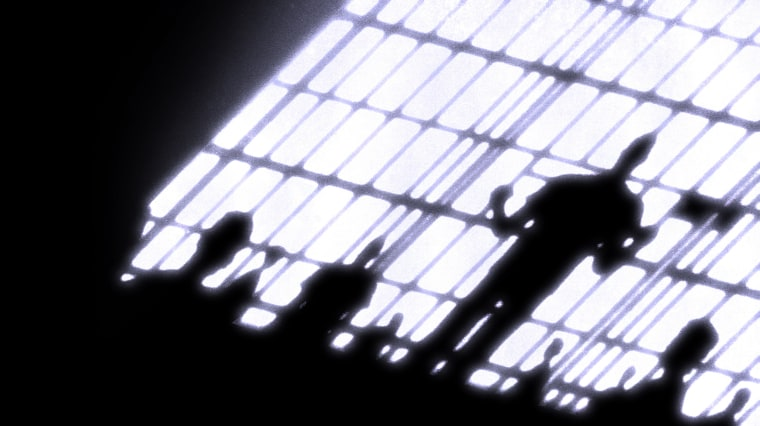 Image: Silhouettes of a prisoners in a packed cell behind bars.