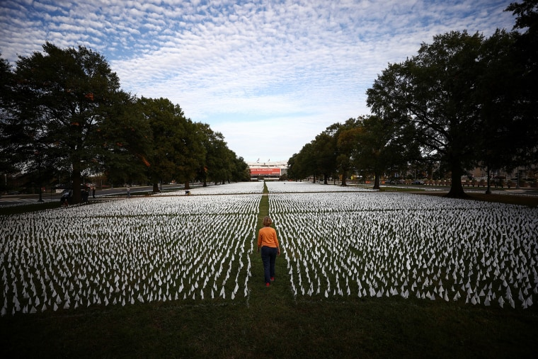"""Image: A person walks past the art installation \""""IN AMERICA How Could This Happen...\"""" by artist Suzanne Brennan Firstenberg, in Washington"""