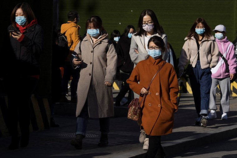 Image: People walk in a street during morning rush hour following an outbreak of the coronavirus disease (COVID-19) in Beijing