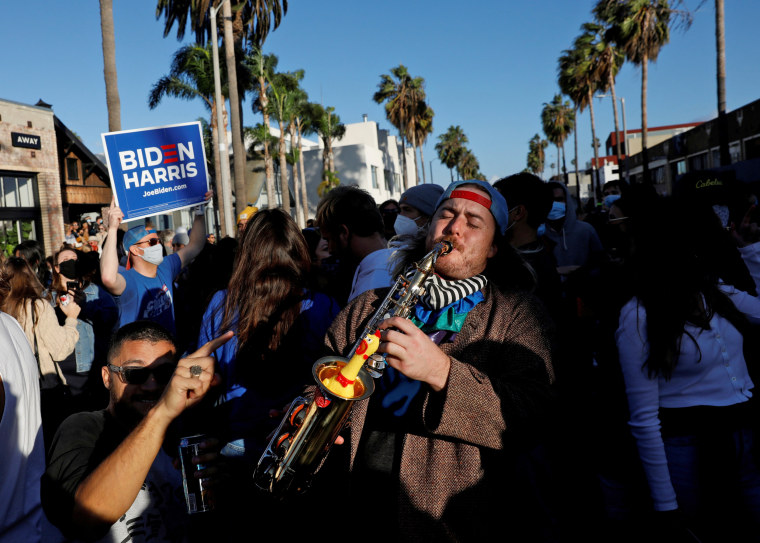 Image: People celebrate after media announced that Democratic U.S. presidential nominee Joe Biden has won the 2020 U.S. presidential election, at Venice Beach, California