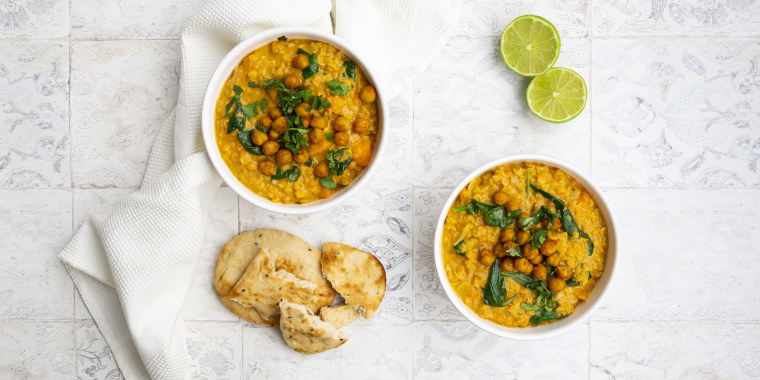 Vegan lentil curry with red lentils, sweet potatoes, spinach, roasted turmeric, chickpeas, with lime juice and coriander and naan bread