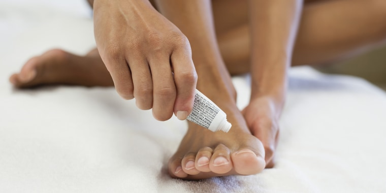 Woman applying ointment to foot, low section