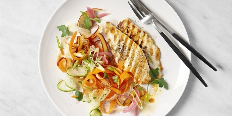 A plate of grilled chicken with carrot salad on white background