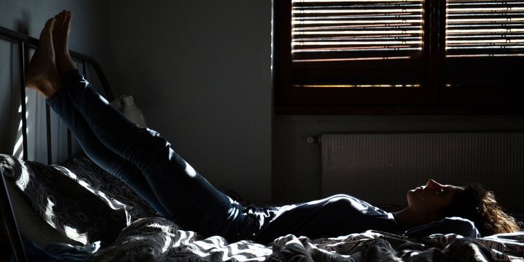 Full Length Of Young Woman Lying On Bed