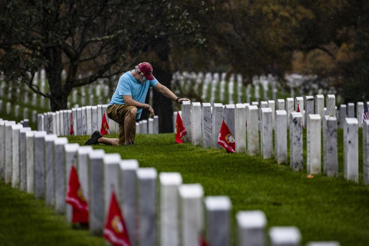 A man kneels in front of a fallen loved one at Arlington National Cemetery on Veterans Day, November 11, 2020 in Arlington, Virginia. Veterans Day is the day when the country honors those who served in the Armed Forces.