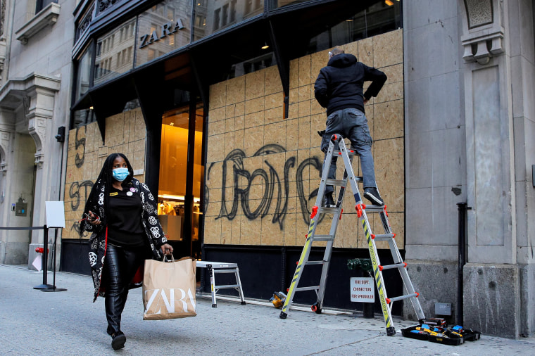 Image: Shopper passes as workers board up a store ahead of election results in Manhattan, New York