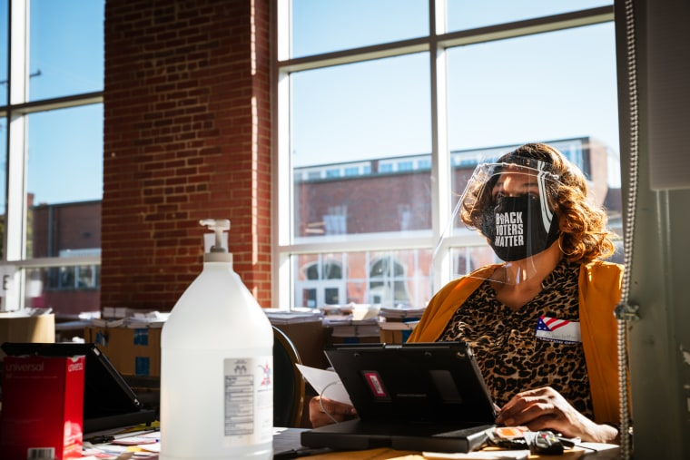 """Image: An election official wearing a mask that reads \""""Black Lives Matter\"""" sits at her desk speaking to a voter"""