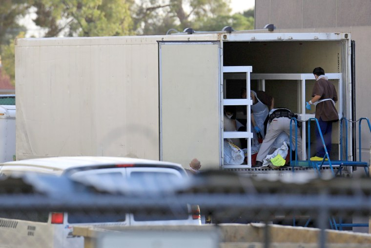 Image: Refrigerated trailers are seen parked at the rear of the El Paso County Office of the Medical Examiner in El Paso