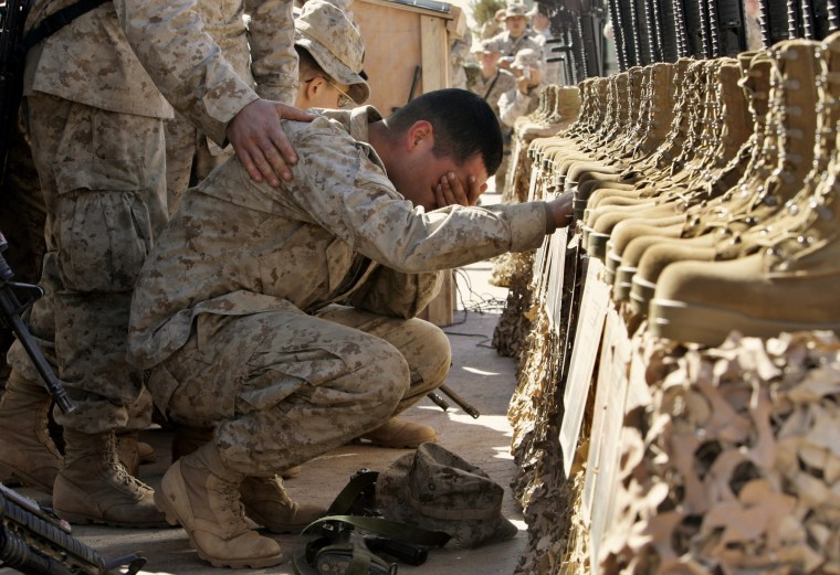 A U.S. Marine cries during the memorial service for 31 killed U.S. servicemen at Camp Korean Village, near Ar Rutbah, western Iraq, on Feb. 2, 2005.