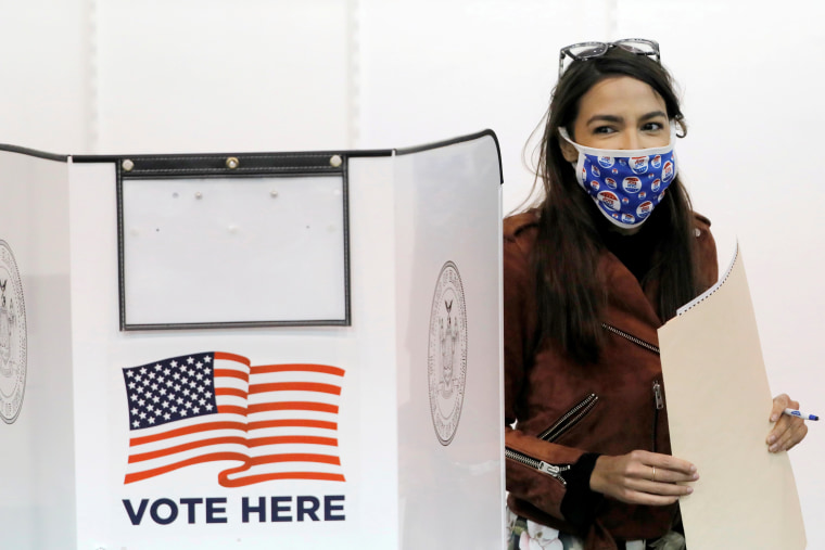 Image: Alexandria Ocasio-Cortez stands next to her voting booth holding her filled ballot.