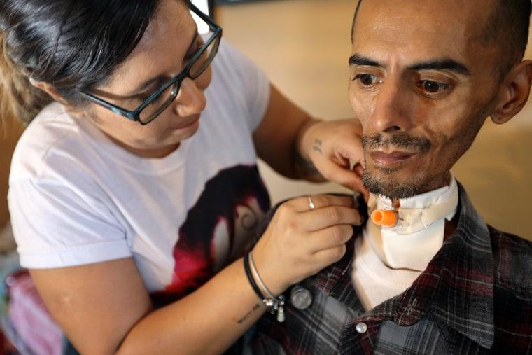 Rocio Alvarado connects her husband Brian's feeding tube at their home in Long Beach, Calif.