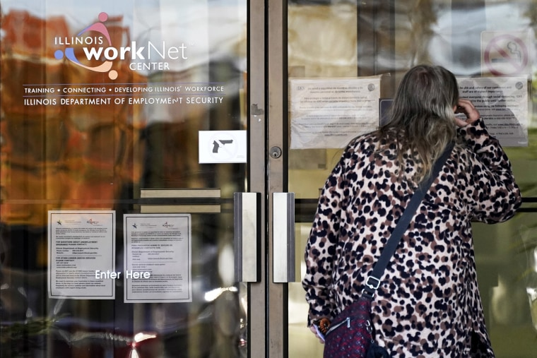 Image: A woman checks information as information signs are displayed at IDES (Illinois Department of Employment Security) WorkNet center in Arlington Heights, Ill