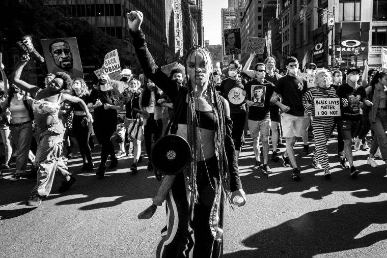 Image: Livia Johnson, an organizer with Warriors in the Garden, raises her fist as she marches with protesters through New York's Times Square on June 14, 2020.