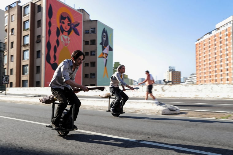 Image: Vinicius Sanctus and Alessandro Russo ride electric monowheels called 'nuvem' (cloud) that were invented by them and inspired by the magic flying brooms of the Harry Potter series in Sao Paulo