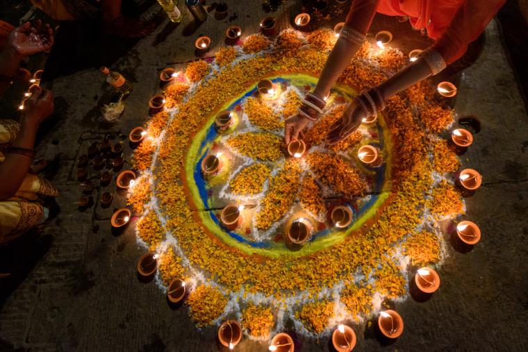 Woman hand lighting diyas during diwali,Varanasi,Uttar Pradesh,India.