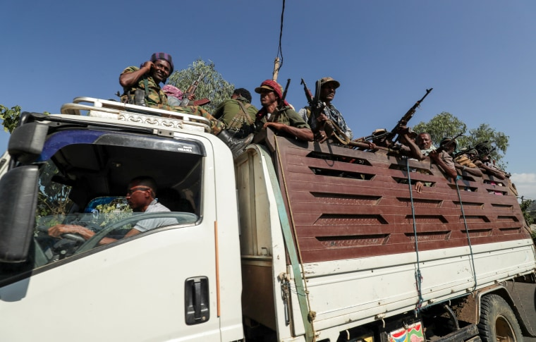 Image: FILE PHOTO: Members of Amhara region militias ride on their truck as they head to face the Tigray People's Liberation Front in Sanja