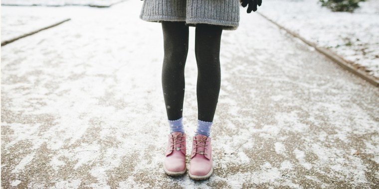 Legs of woman standing in snow