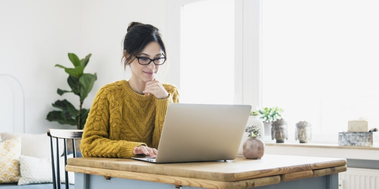 Image: Woman sitting at table, using laptop