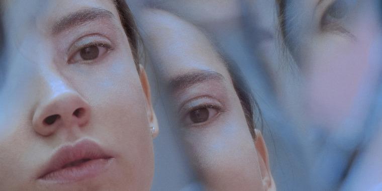 Multiple reflection of female face in broken mirror