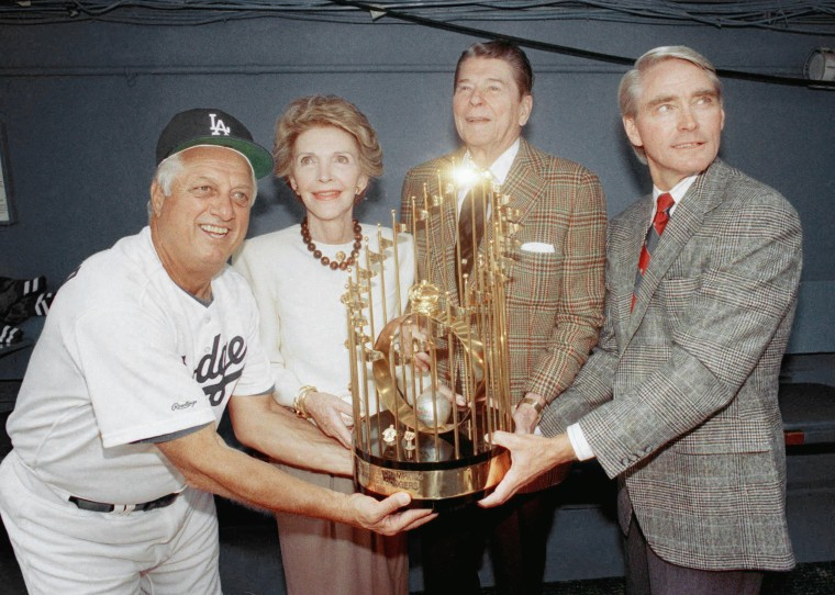 Dodgers manager Tommy Lasorda, left, shares one of the Los Angeles Dodgers' World Championship trophies with former President Ronald Reagan, Nancy Reagan, and Dodgers executive vice-president Fred Claire, right, before home opener at Dodger Stadium in Los Angeles on April 13, 1989.