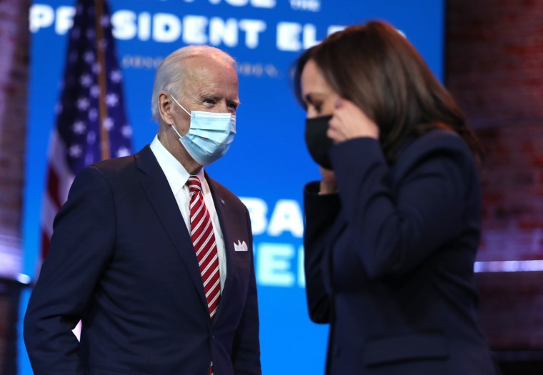Image: President-elect Joe Biden walks by Vice President-elect Kamala Harris during a press briefing at the Queen Theater