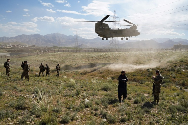 Image: A U.S. military Chinook helicopter lands on a field outside the governor's palace during a visit by the commander of U.S. and NATO forces in Afghanistan