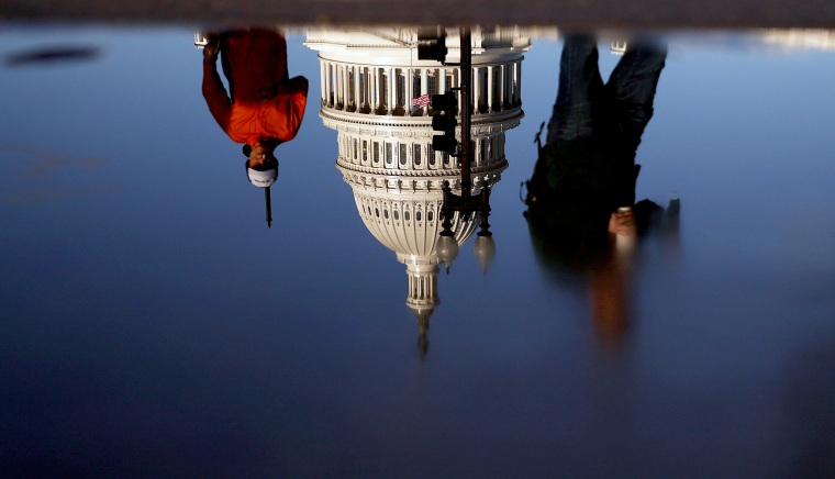 Image: U.S. Capitol is seen reflected in a puddle in Washington