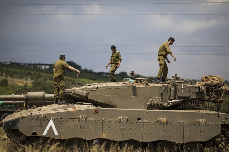 Image: Israeli soldiers on top of a Merkava Mark IV tank that deployed along the border with Syria, in Golan Heights, Israel.