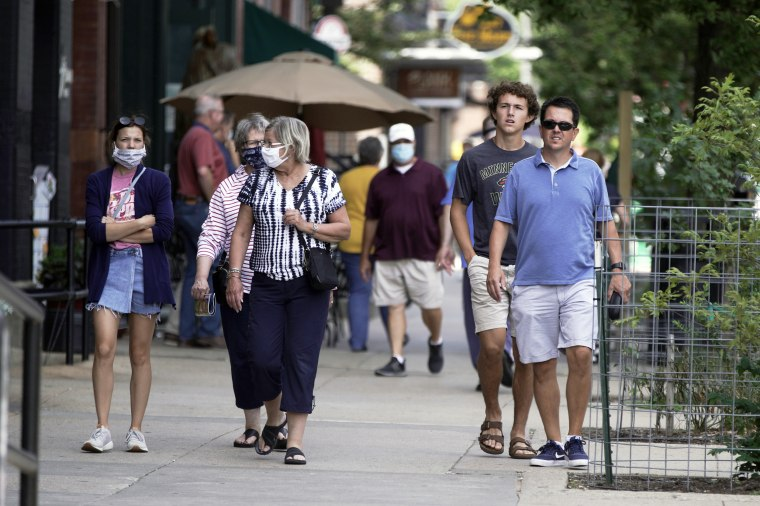 Pedestrians with and without face masks walk in downtown Omaha, Neb., on July 31, 2020.