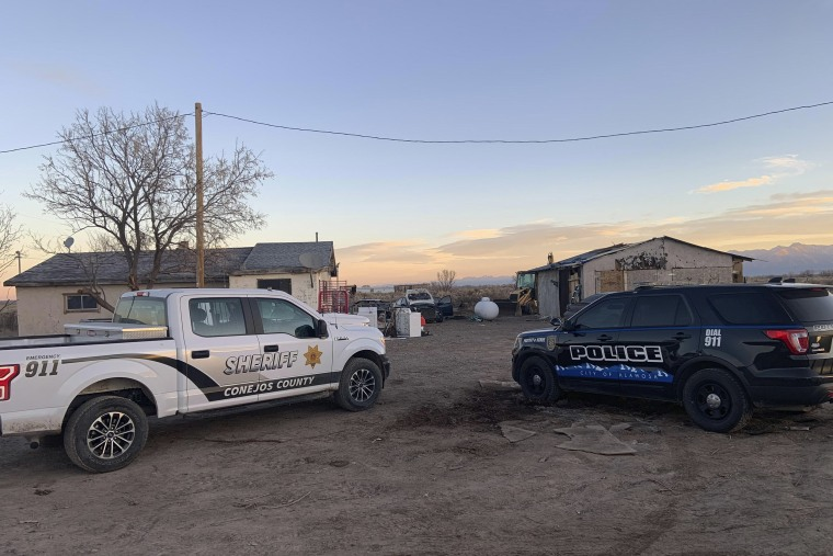 Image: Law enforcement vehicles are parked at on one two properties where skeletal remains were found about 20 miles (32 kilometers) south-southeast of Alamosa, Colo