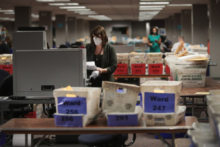 Image: Claire Woodall-Vogg, executive director of the Milwaukee election commission collects the count from absentee ballots from a voting machine