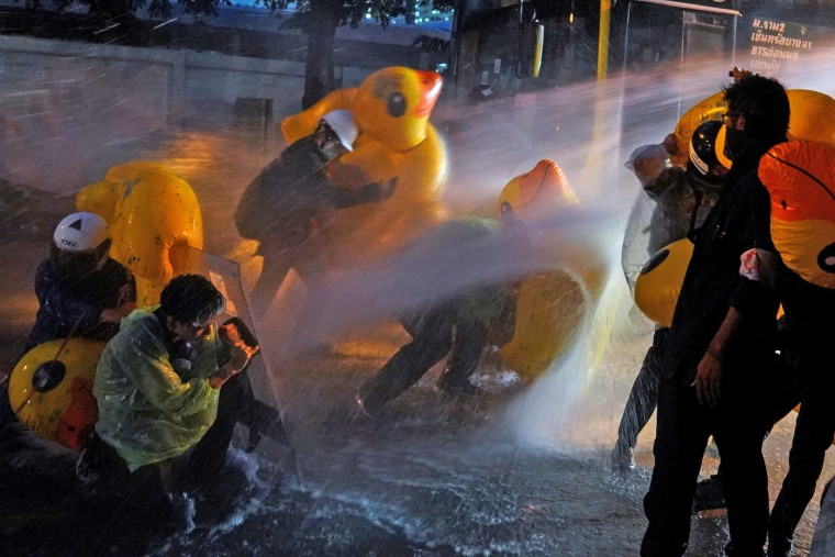 Image: Demonstrators use inflatable rubber ducks as shields to protect themselves from water cannons during an anti-government protest, outside the parliament in Bangkok