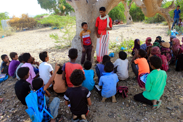 Image: Displaced Yemeni children attend an open air class in the shade of a tree in the district of Abs in the northern Hajjah province