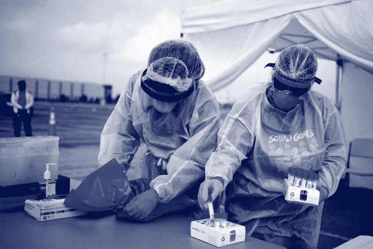 Image: Healthcare workers prepare specimen collection tubes at a coronavirus disease (COVID-19) drive-thru testing location in Houston