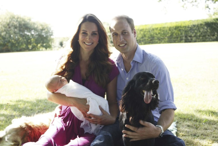 Britain's Prince William and his wife Catherine, Duchess of Cambridge, pose with their son Prince George in the garden of the Middleton family home in Bucklebury, southern England