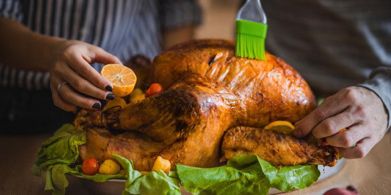 Close up of unrecognizable couple preparing Thanksgiving turkey.