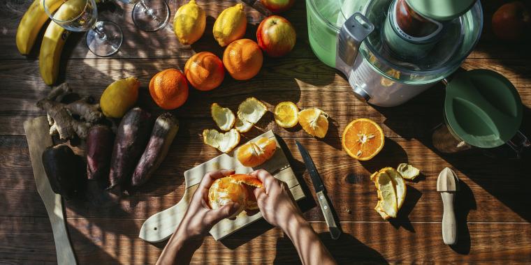 Woman's hands peeling orange for squeezing juice