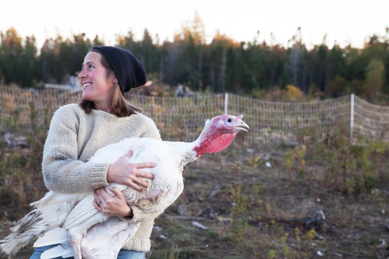 Carly DelSignore holds a turkey at Tide Mill Organic Farm, which she runs with her husband, Aaron Bell, in Edmunds, Maine.