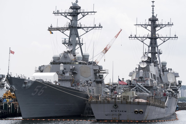 Image: The USS John S. McCain (DDG 56) destroyer (L) is moored in a dock at the Yokosuka Naval Base