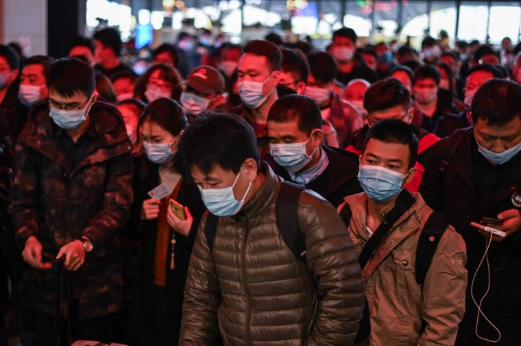Image: Passengers wearing face masks as a preventive measure against the Covid-19 coronavirus walk to their train at Wuhan railway station in Wuhan, China's central Hubei province