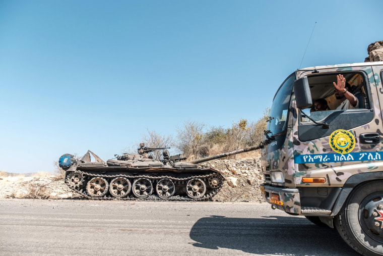Image: A damaged tank stands abandoned on a road as a truck of the Amhara Special Forces passes by near Humera, Ethiopia