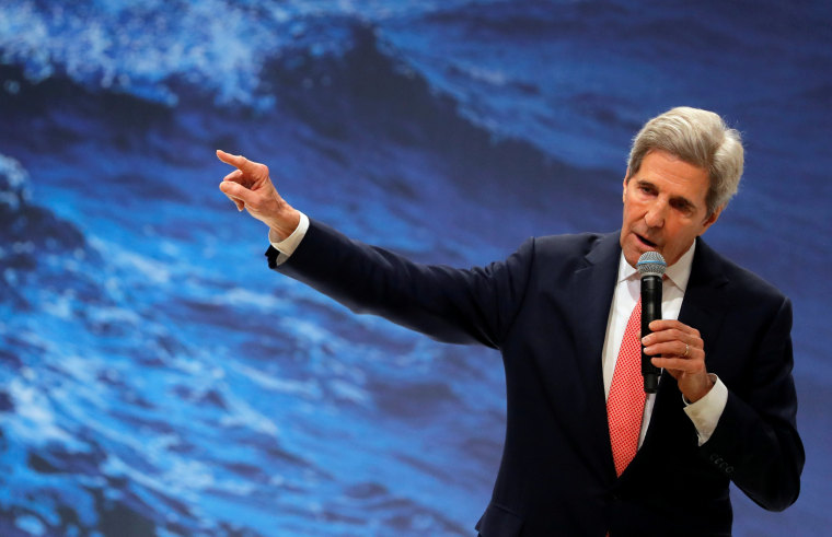 Image: John Kerry holding a mic against a background of waves