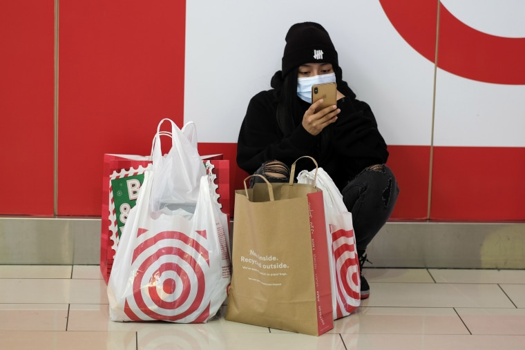 Image: A Black Friday shopper wearing a face mask rests at the Glendale Galleria in Glendale