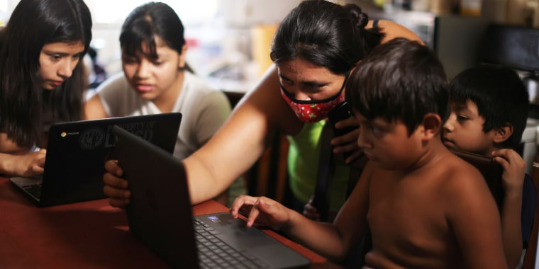 Los Angeles Unified School District students Keiley Flores, 13, Andrea Ramos, 10, and Alexander Ramos, 8, work on school-issued computers with unreliable internet connectivity, as their mother Anely Solis, 32, and their brother Enrique Ramos, 5, look on.